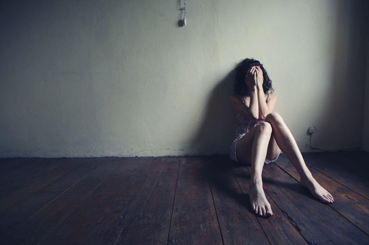 Woman in pain in an empty room