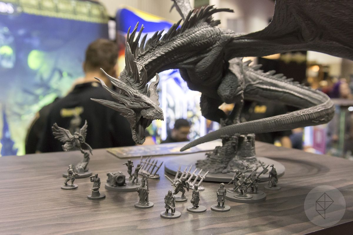 A massive dragon towers over a group of peasants in an early model from the Joan of Arc line of miniatures.