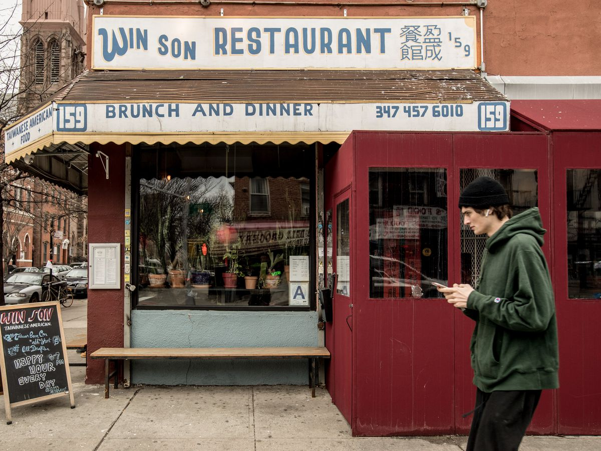 The old-school, deli-like exterior of Win Son, with a pedestrian crossing in front of the restaurant