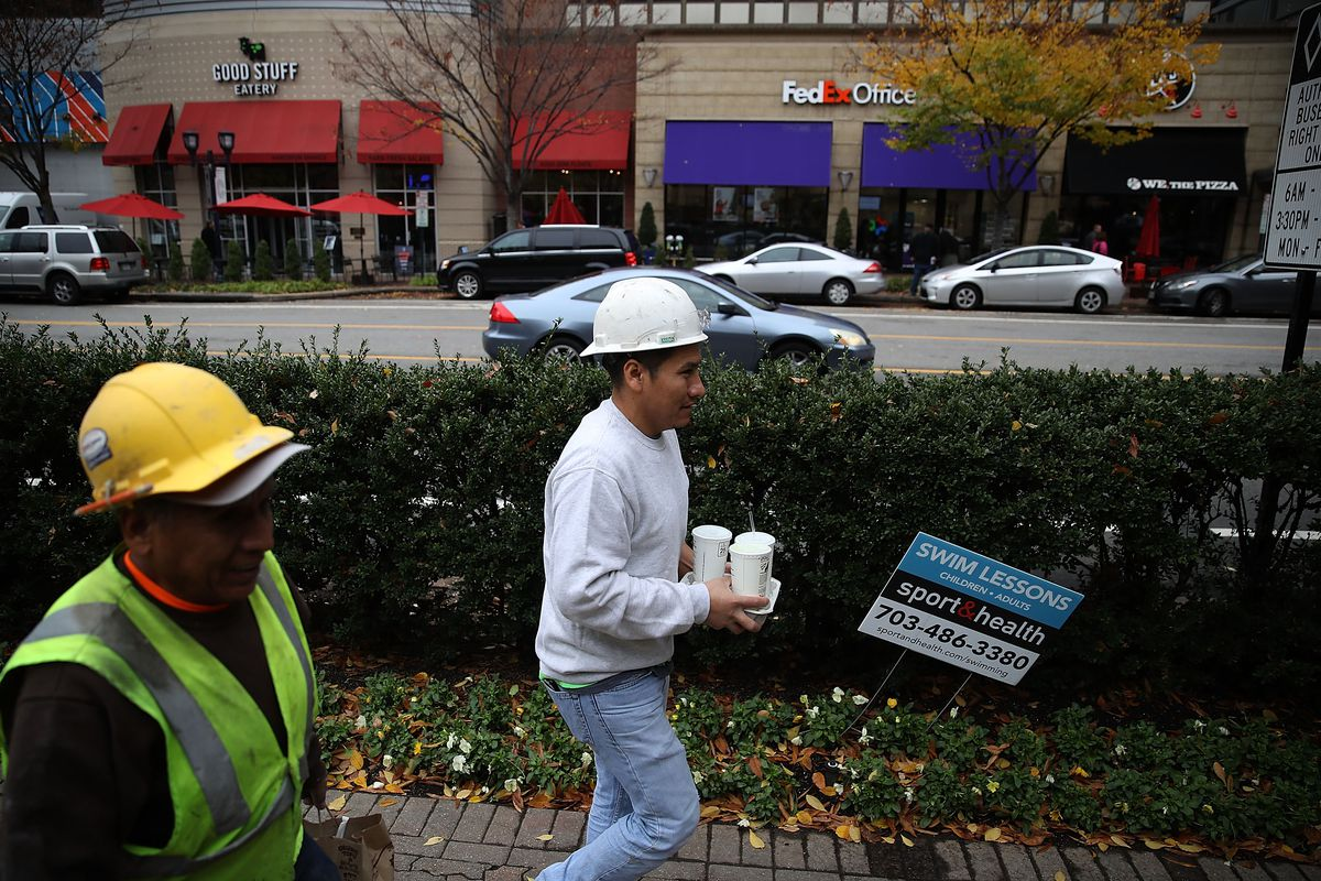 Men walk along Crystal Drive in the Crystal City area on November 13, 2018 In Arlington, Virginia. Amazon announced today that it has chosen Crystal City in Arlington, Virginia and Long Island City in Queens, New York as the two locations which will both