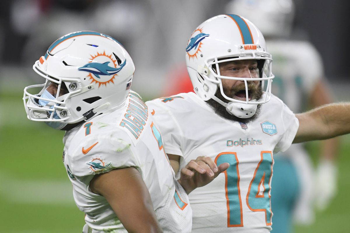 Ryan Fitzpatrick #14 of the Miami Dolphins celebrates his touchdown pass with Tua Tagovailoa #1, to take a 23-22 lead over the Las Vegas Raiders, during the fourth quarter at Allegiant Stadium on December 26, 2020 in Las Vegas, Nevada.
