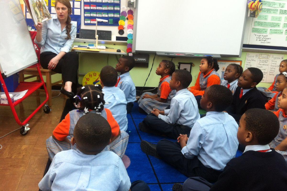A third-grade teacher at Success Academy, reads to her students.