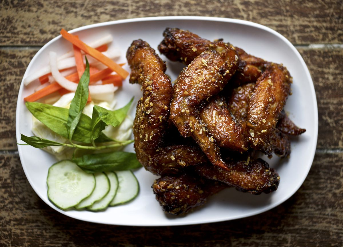 A plate of chicken wings with carrots, cucumbers, and more on the left