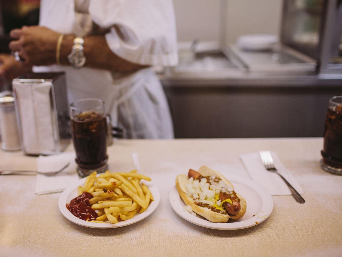 fries with ketchup on the side and a coney dog on a white diner counter with a man's arm in the background