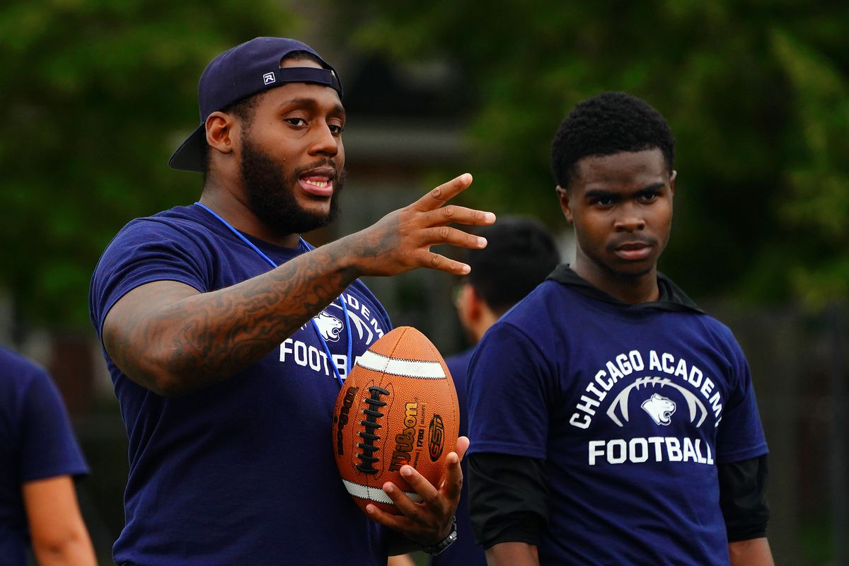 Chicago Academy coach Anthony Dotson instructs QB Earnest Davis on how to pass to his receivers during football practice in Chicago, Thursday, July 15, 2021.