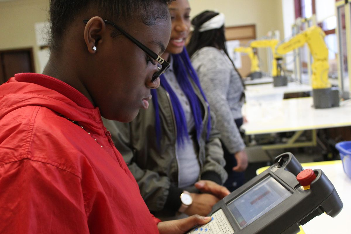 Cheyanne Robinson, a junior at Denby High School, practices with a robotic arm donated by the manufacturer FANUC.