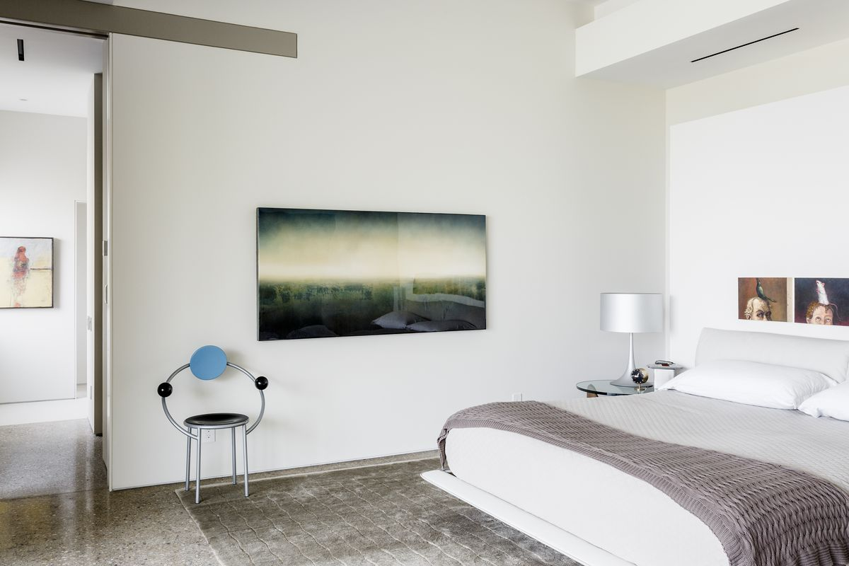 A bedroom is filled with art, with a modern, circular chair; a green abstract landscape; and a pair of portraits.