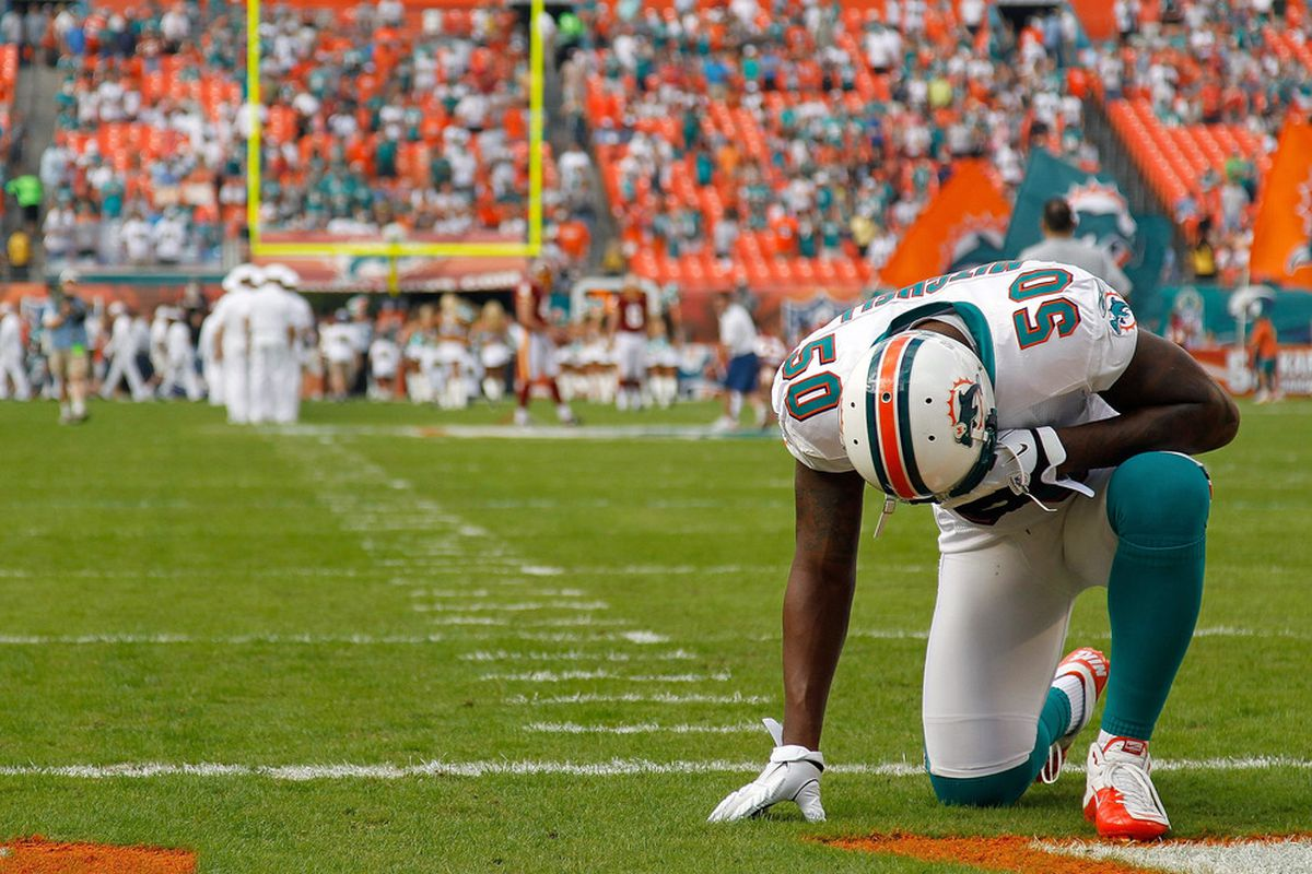 MIAMI GARDENS, FL - NOVEMBER 13:  Marvin Mitchell #50 of the Miami Dolphins prays during a game against the Washington Redskins at Sun Life Stadium on November 13, 2011 in Miami Gardens, Florida.  (Photo by Mike Ehrmann/Getty Images)