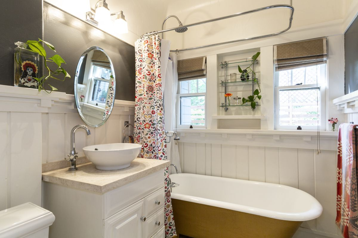Bathroom with a round mirror, two windows, and a freestanding tub.