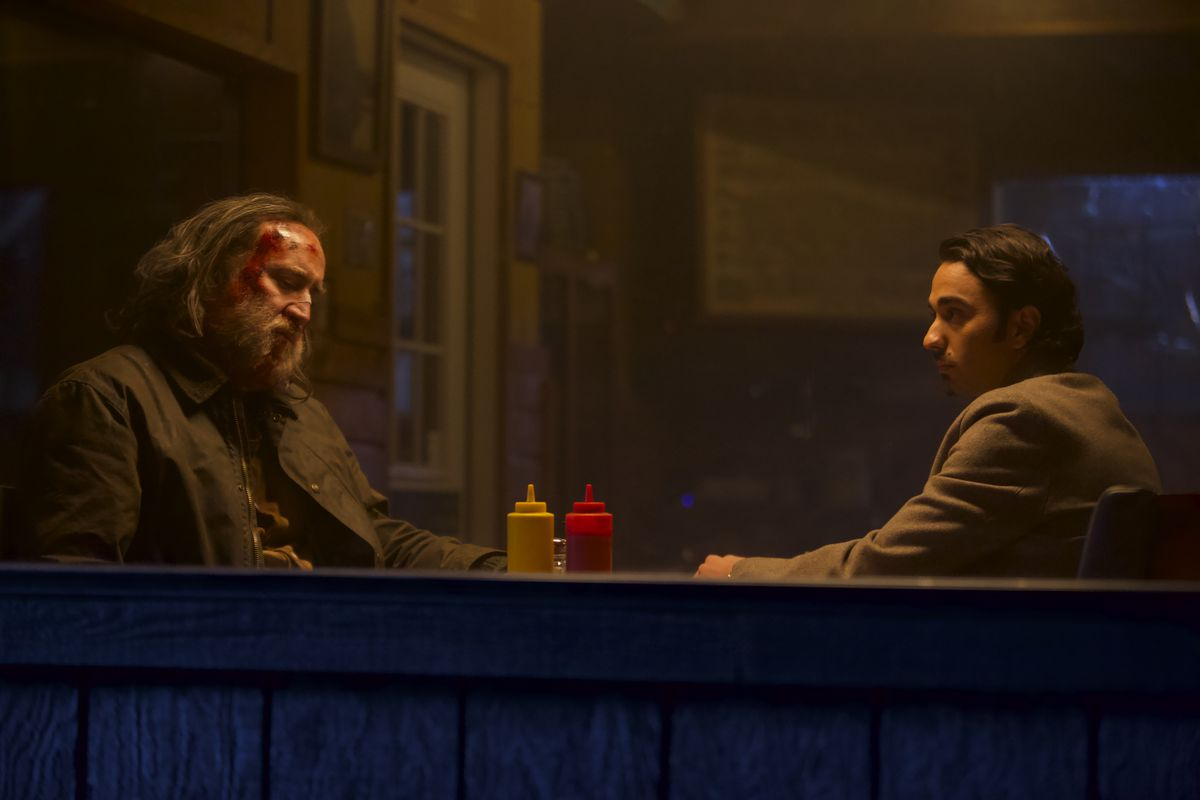 A still from 'Pig' featuring Nicolas Cage and Alex Wolff sitting in a diner.