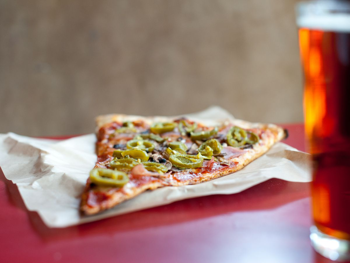 Slice of pizza with glass of beer