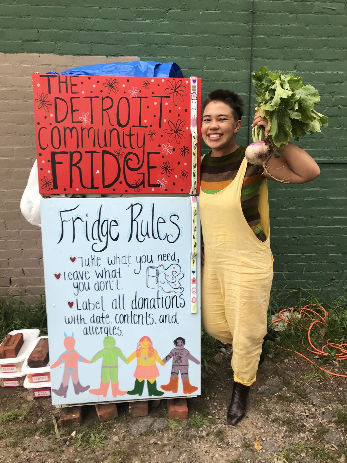 """A person holding up a turnip with greens stands beside a sign that reads """"The Detroit community fridge. Fridge rules: Take what you need, leave what you don't. Label all donations with date and contents and allergies."""""""
