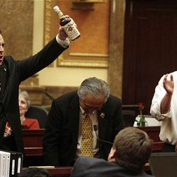 Rep. Greg Hughes, R-Draper, left, holds up a bottle of alcohol presented to him by Rep. Curtis Oda, R-Clearfield, center, and Rep. John Dougall, R-Americn Fork, as the final session of the 2009 Utah Legislature is adjourned at the Capitol Thursday.