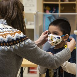 Preschool teacher Erin Berry helps a student with his face mask during class Monday morning at Dawes Elementary School at 3810 W. 81st Pl. on the Southwest Side.