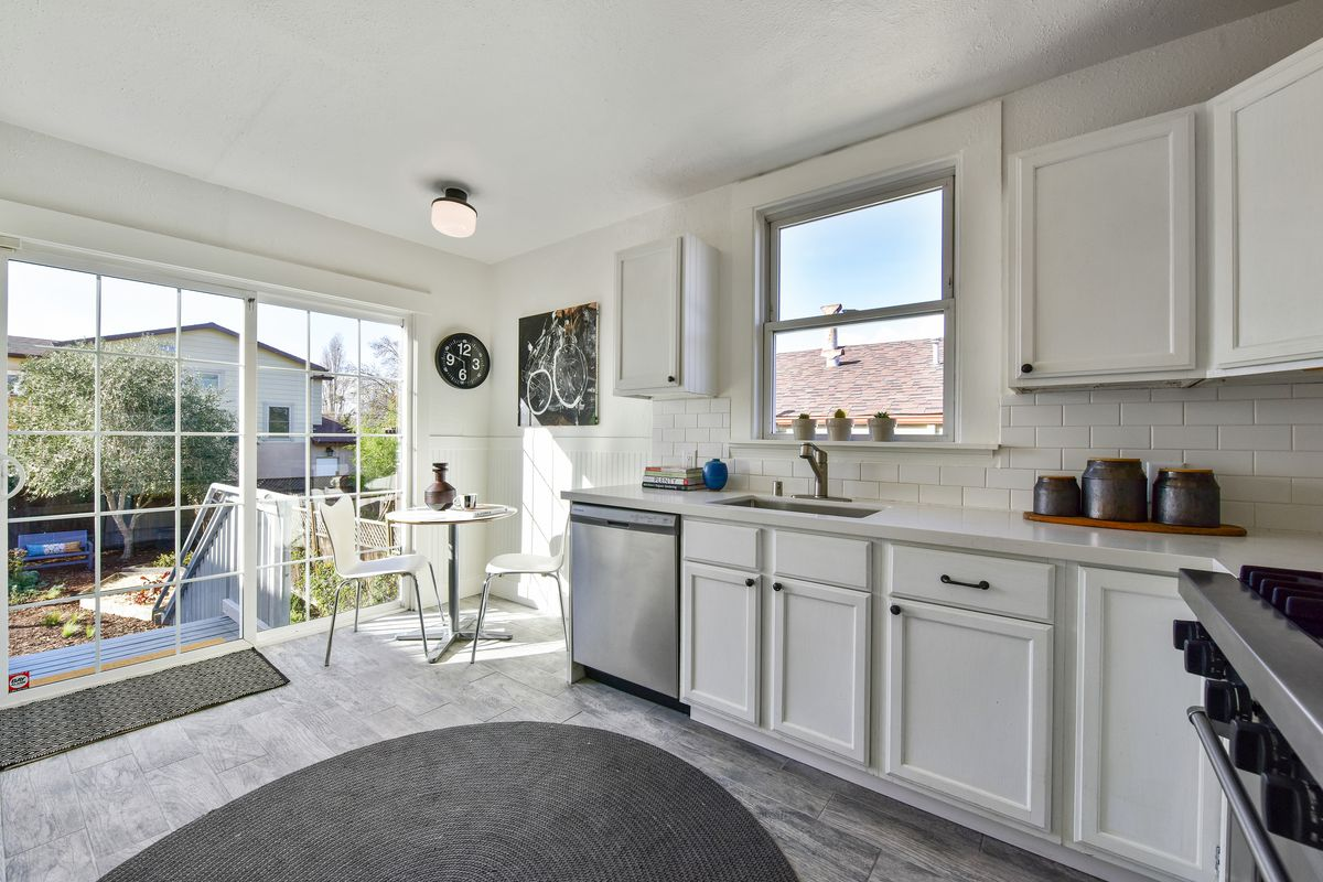 A kitchen with white walls, stainless steel appliances, and sliding glass doors.