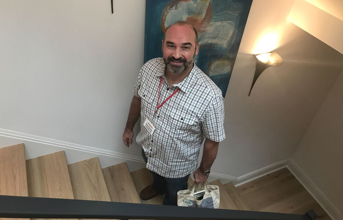"""<p><span style=""""font-size:18px""""><strong>One Step at a Time</strong></span></p> <p>One noticeable design feature in the home is the sleek, modern railings. Greg Flessate from Chantilly, VA is seen here demonstrating the vast amount of levels in the Idea House as his wife Kristen admires the glassware in the kitchen. Greg and his wife have a lot in common – both of their fathers were architects, and they similarly grew up loving home improvement and watching <em>This Old House</em>. Greg's biggest"""