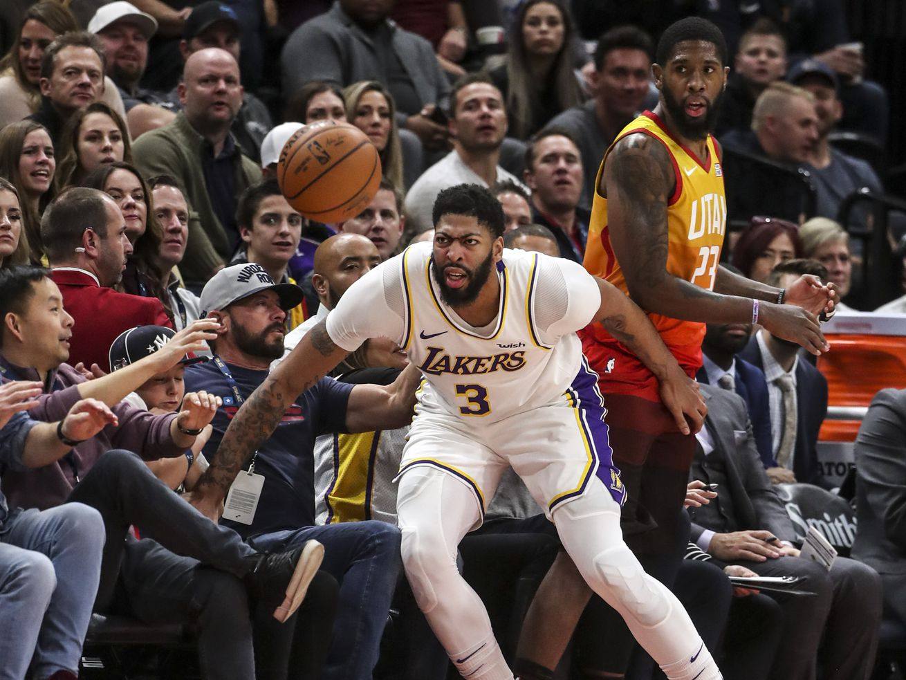 Los Angeles Lakers forward Anthony Davis (3) crashes out of bounds with Utah Jazz forward Royce O'Neale (23) during an NBA basketball game at Vivint Arena in Salt Lake City on Wednesday, Dec. 4, 2019.