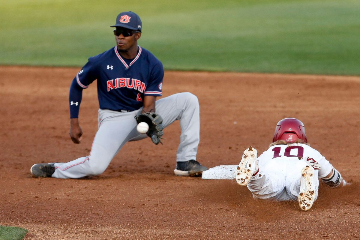 Auburn shortstop Ryan Bliss takes a throw too late as Alabama base runner Jim Jarvis (10) steals second in Sewell-Thomas Stadium