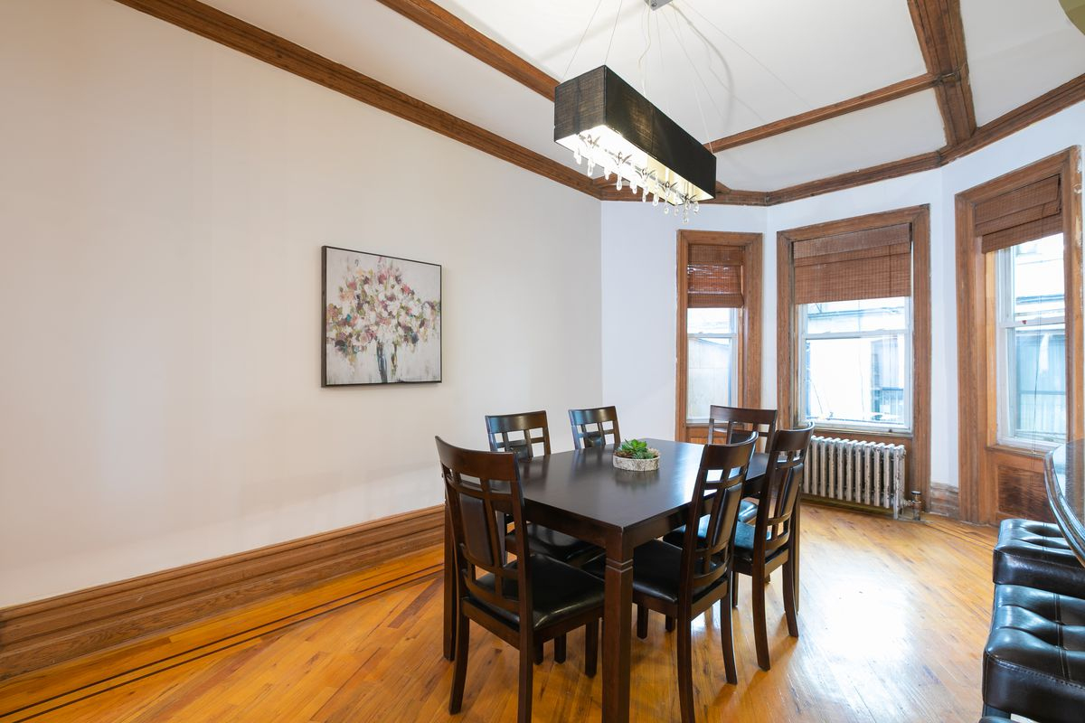 A dining area with hardwood floors, a table, and three windows.