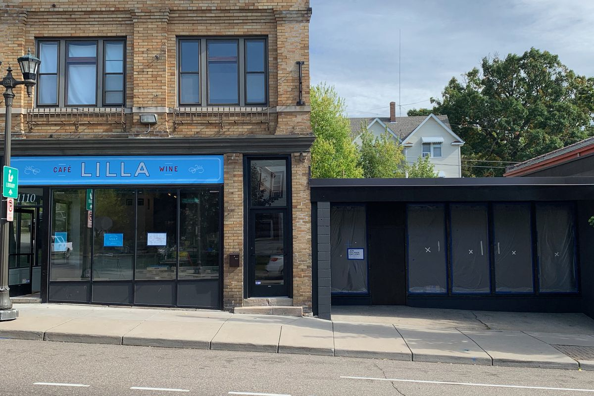A blue and black lettered storefront for the restaurant and gallery, Cafe Lilla