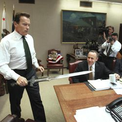 """FILE - In this Jan. 13, 2009 file photo, Gov. Arnold Schwarzenegger brings the sword he used in the movie """"Conan The Barbarian,"""" to the conference table before the start of budget negotiations with legislative leaders at the Capitol in Sacramento, Calif. Schwarzenegger, who came to office during California's historic 2003 recall election, will  soon be releasing his autobiography, """"Total Recall: My Unbelievably True Life Story."""""""