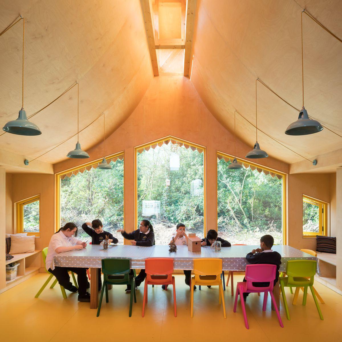 School children sitting inside school on colorful chairs