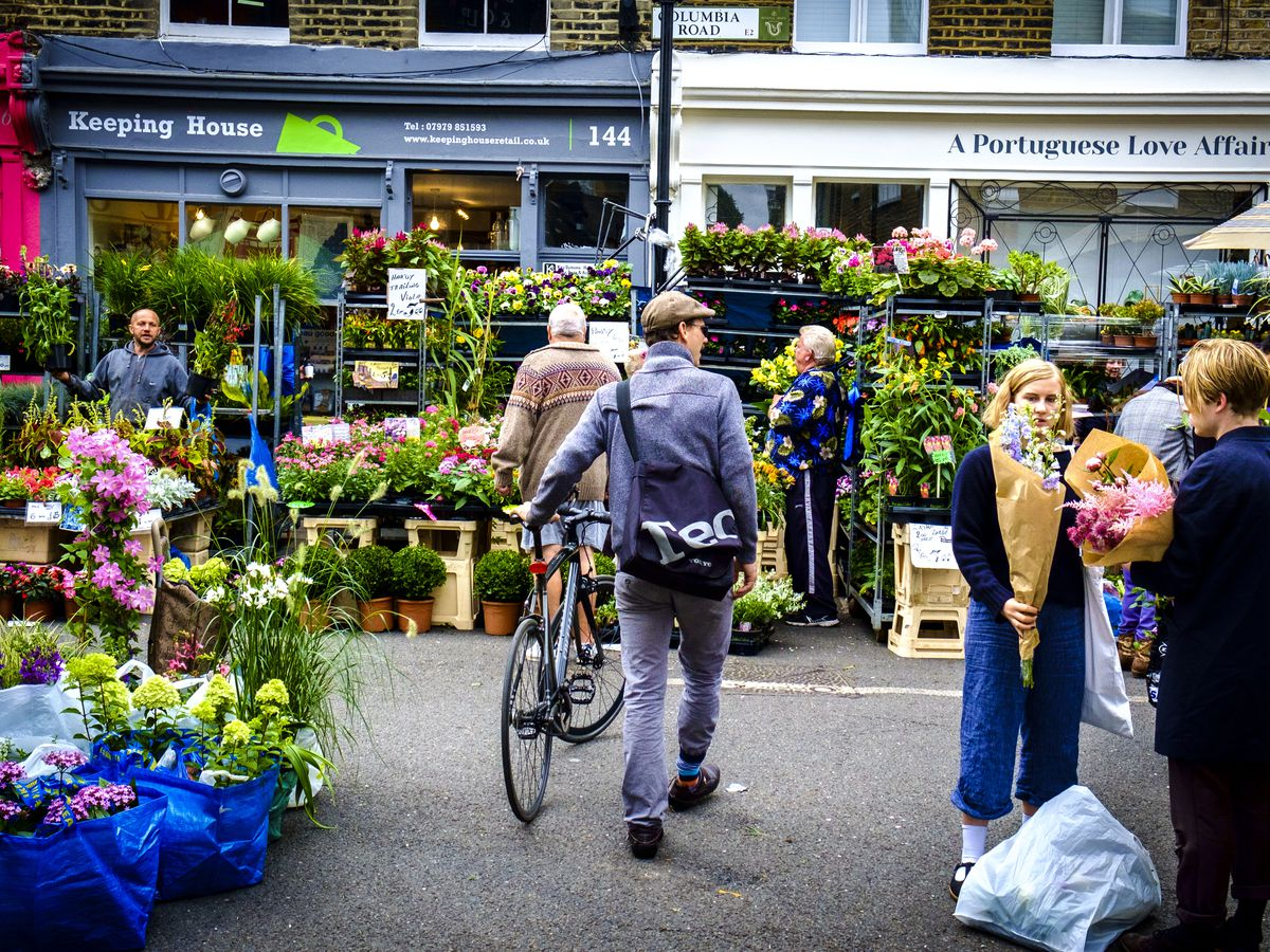 A person walks a bicycle alongside stalls full of flowers and plants at the Columbia Road Flower Market in London.