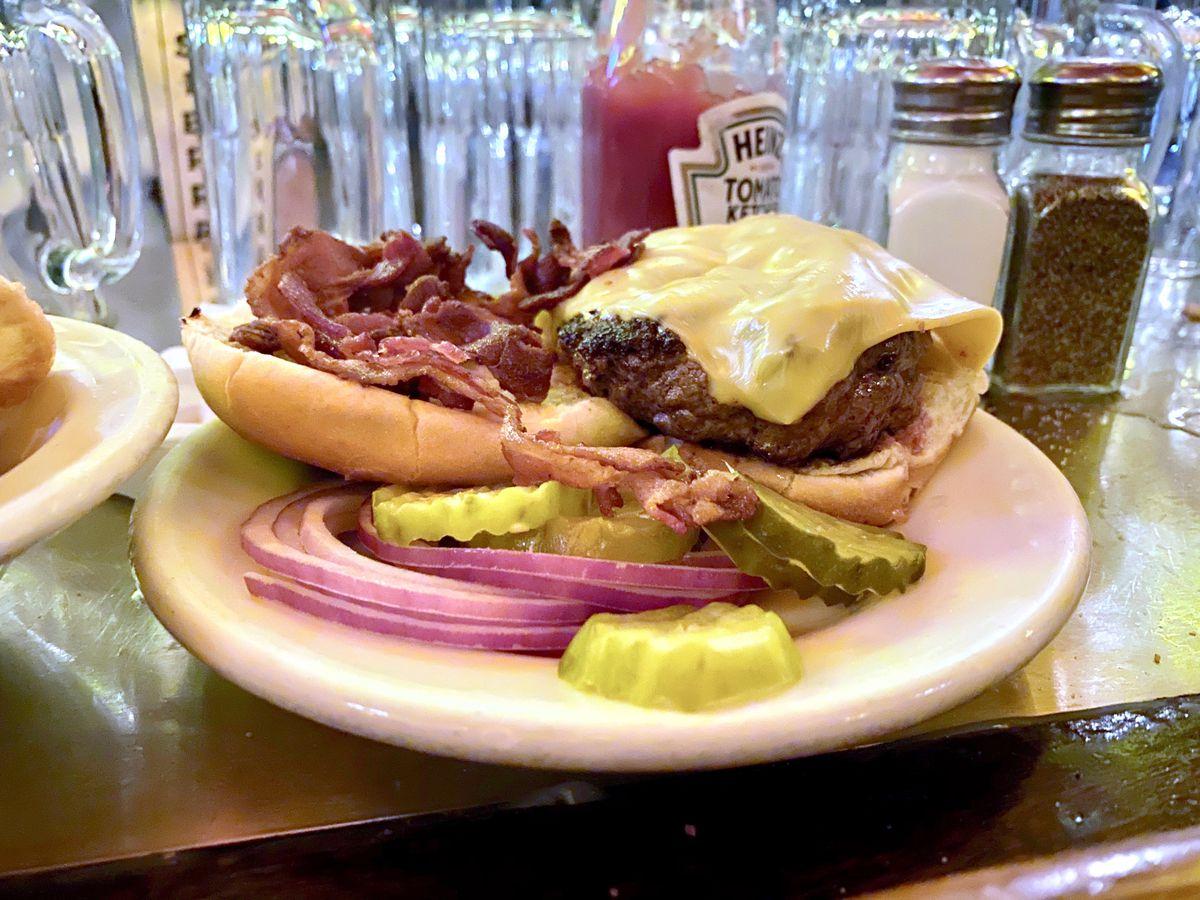 A bacon cheeseburger sits on a white plate at J.G. Melon's bar