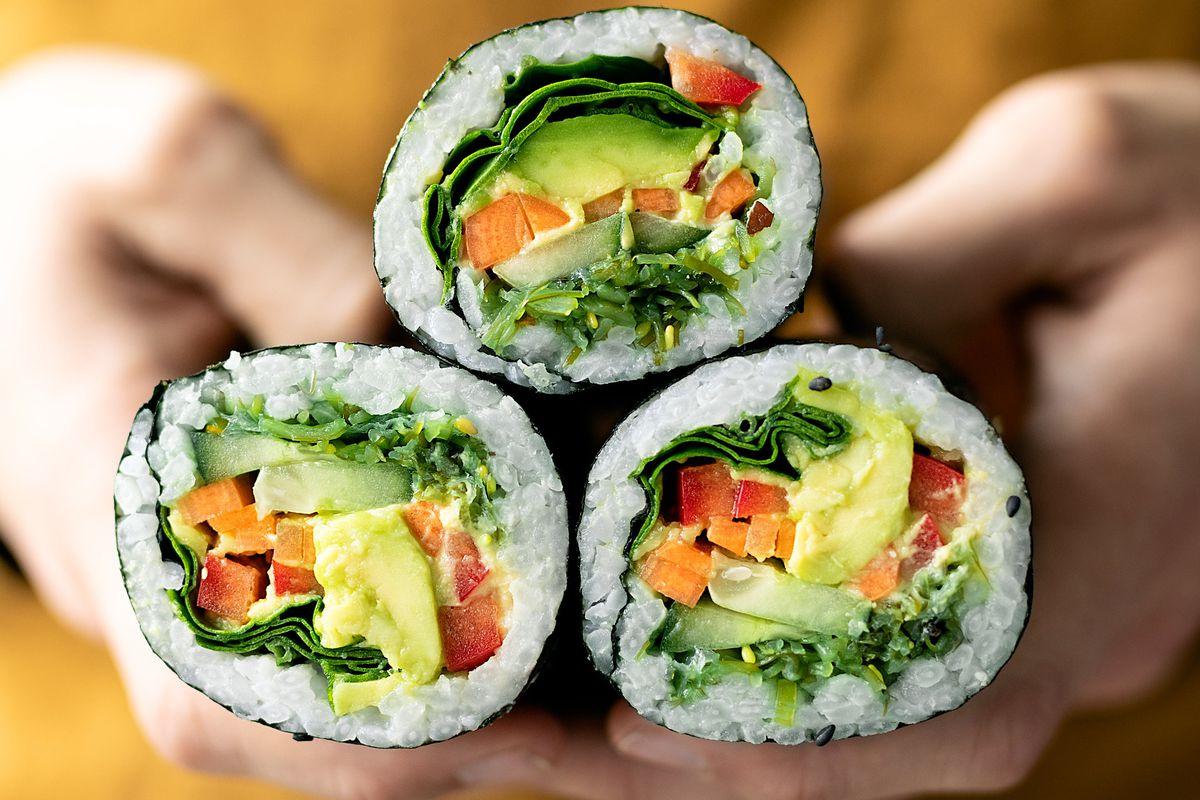 Hands holding three Japanese hand rolls with veggies inside.
