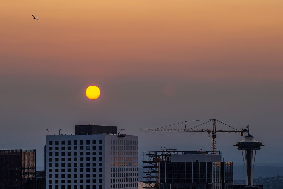 The Space Needle, a construction crane, and some buildings underneath a smoky backdrop, with a red sun.
