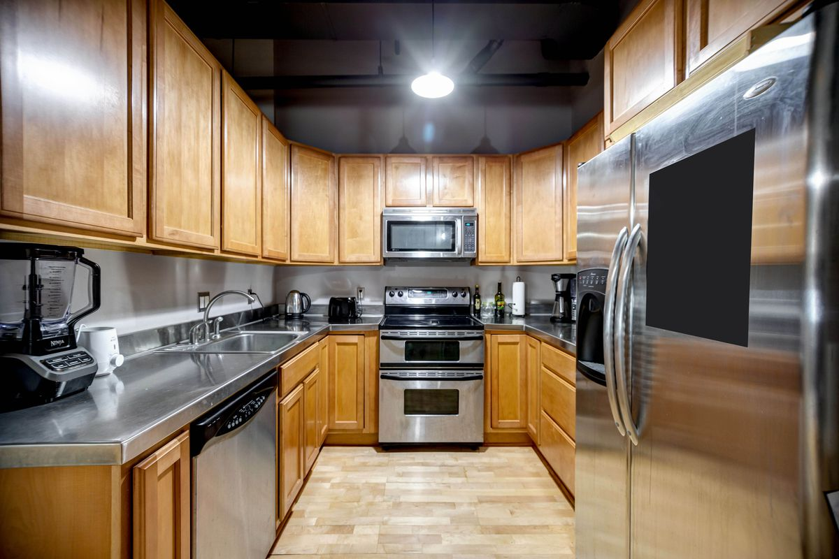 Rectangular kitchen with stainless steel countertops and appliances, and wood cabinets.