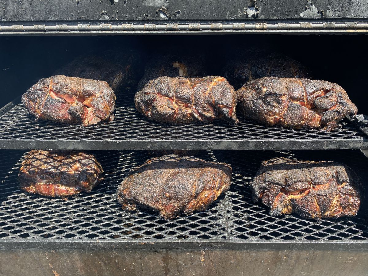 Crusted pork shoulders on an offset smoker, being barbecued.