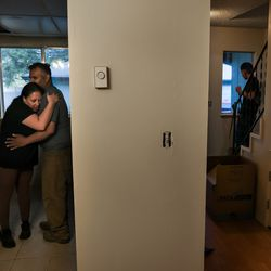 Laura Avalos and Yakson Chavez embrace in the kitchen of their new apartment while Avalos' son, Diego Rodriguez, 16, right, sweeps the floor in Phoenix, Ore., on Wednesday, Sept. 23, 2020. The family lost their home in Phoenix in the Almeda Fire and have received help finding housing and with other needs from a network of women aiming to assist migrant and Latino families who were impacted by the fire.