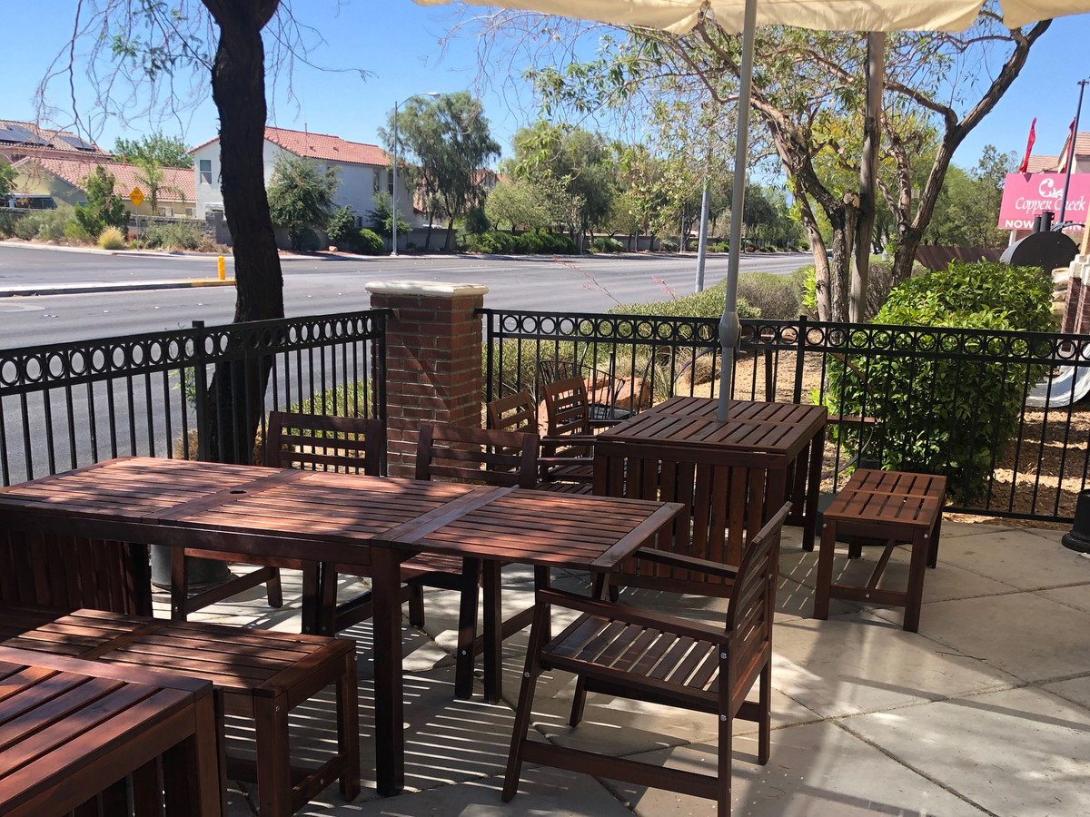 A patio with tables and umbrellas