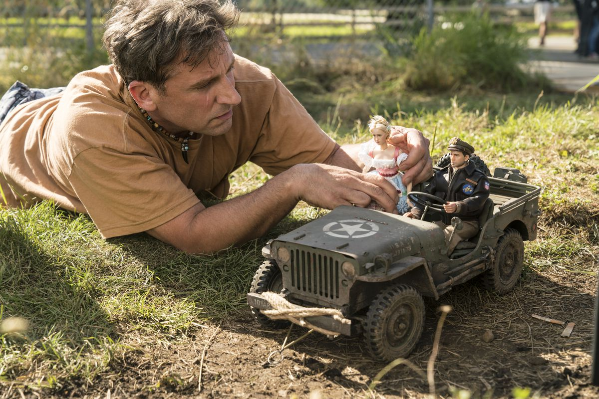 """Steve Carell as Mark Hogancamp photographs the dolls for his fictional town in """"Welcome to Marwen,"""" directed by Robert Zemeckis."""
