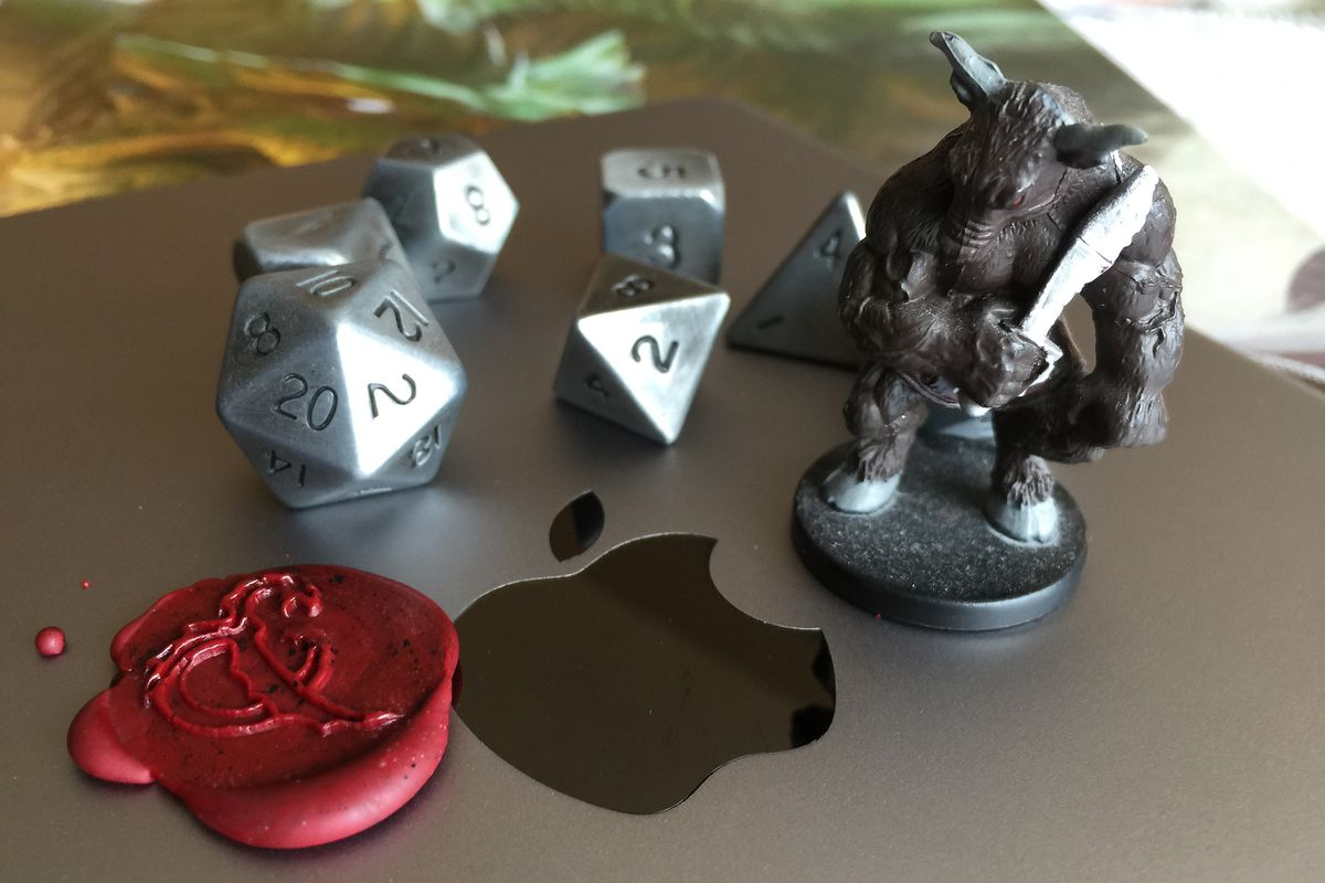 Dice and a miniature beside a wax seal of the D&D logo on the lid of a Mac notebook.