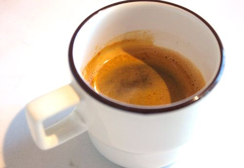 A small white cup with a dark rim is half-filled with espresso