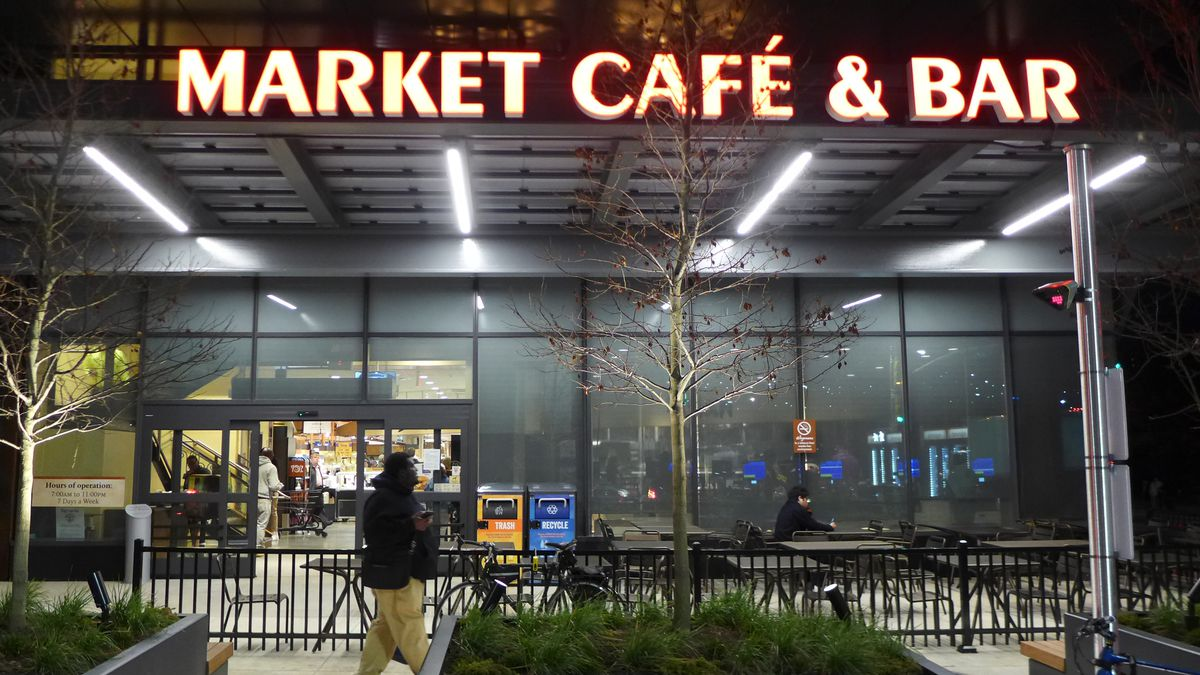 By night the darkened entrance to Wegmans food court, with a shadowy figure walking by in front.