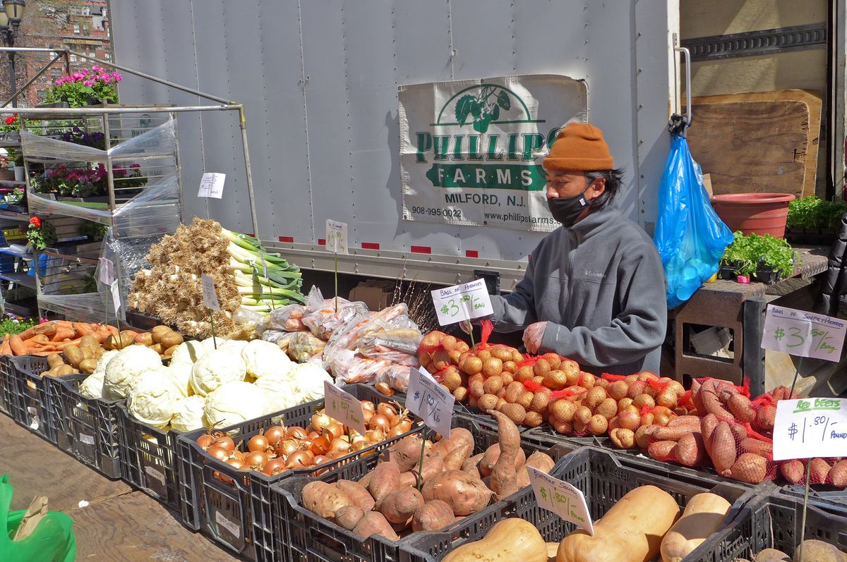 A man stands behind a counter displaying cabbages and potatoes.