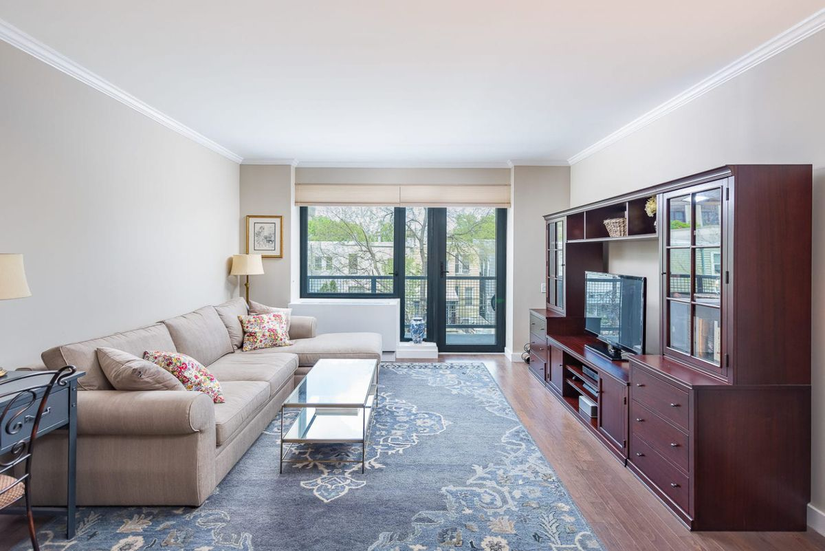 A living area with hardwood floors, a large rug, wooden shelves, a beige couch, and a door that leads to a balcony.