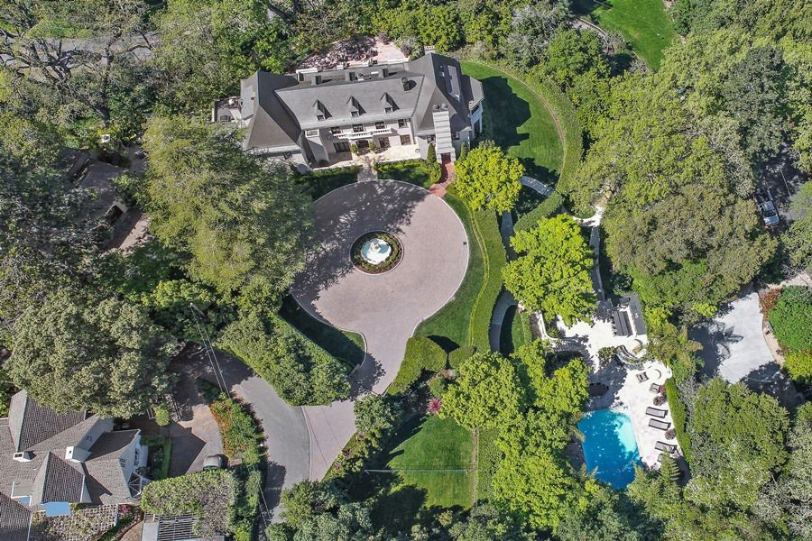 A aerial photo of a forested estate with a two-story white mansion and circular brick driveway.