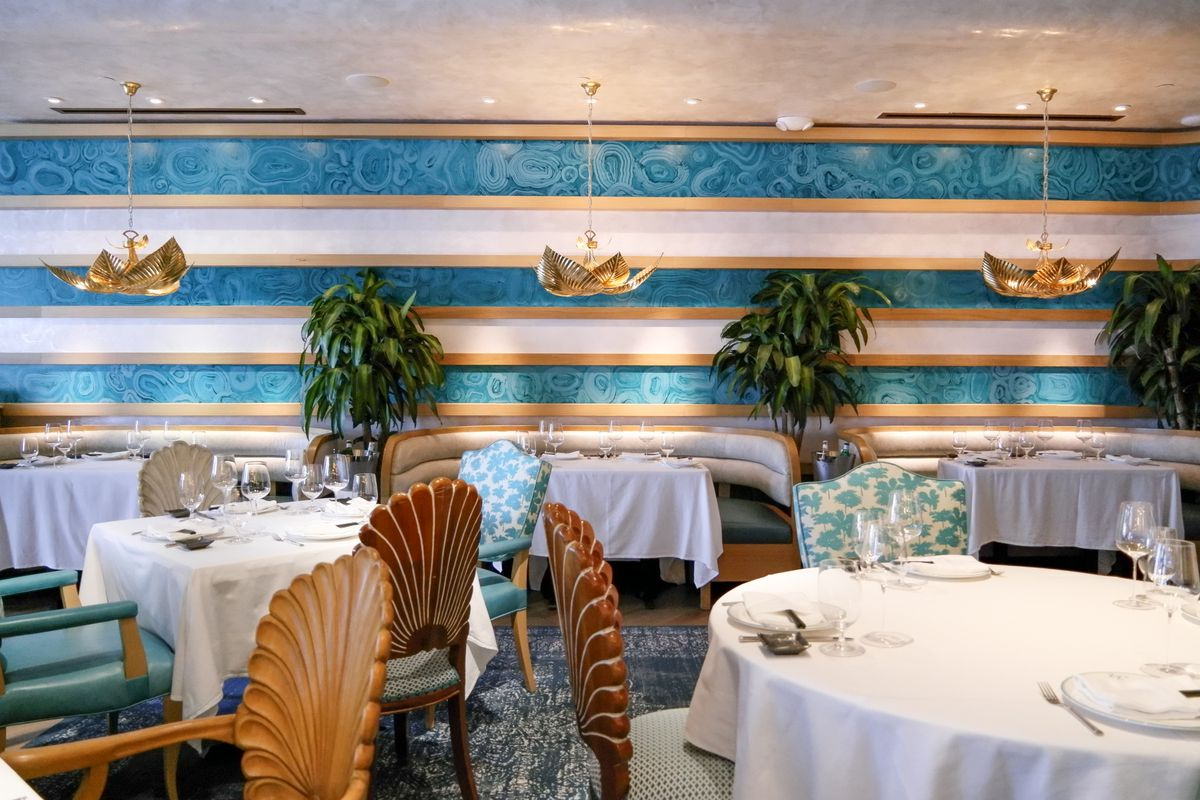 blue and white striped wall with chairs in the front and gold chandeliers