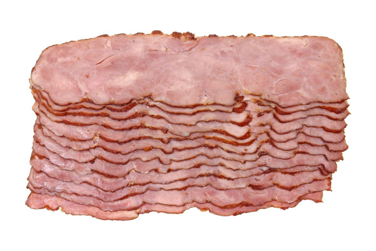 Overhead photo showing shingled slices of raw turkey bacon against a white background.