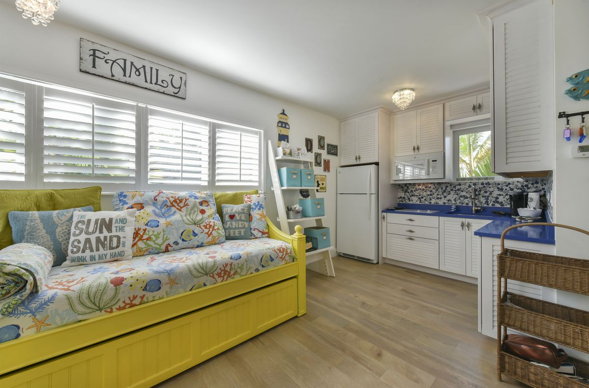 A yellow day bed with fish linens sits in a white and blue guest cottage with kitchenette.