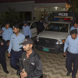 Police officers escort a vehicle carrying the family of Osama bin Laden, in Islamabad, Pakistan on Thursday, April 26, 2012. A van carrying the three widows and children of Bin Laden has left the house where they have been staying in Islamabad and is en route to the airport, from where they will be deported to Saudi Arabia, officials and witness said.