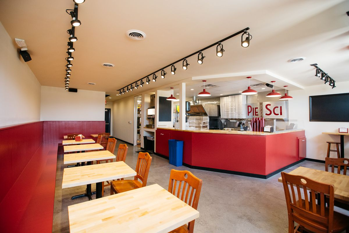 A wide view of two top tables along the wall in the red and white dining room at Pie-Sci