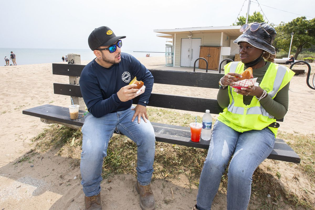 two city workers eat hot dogs