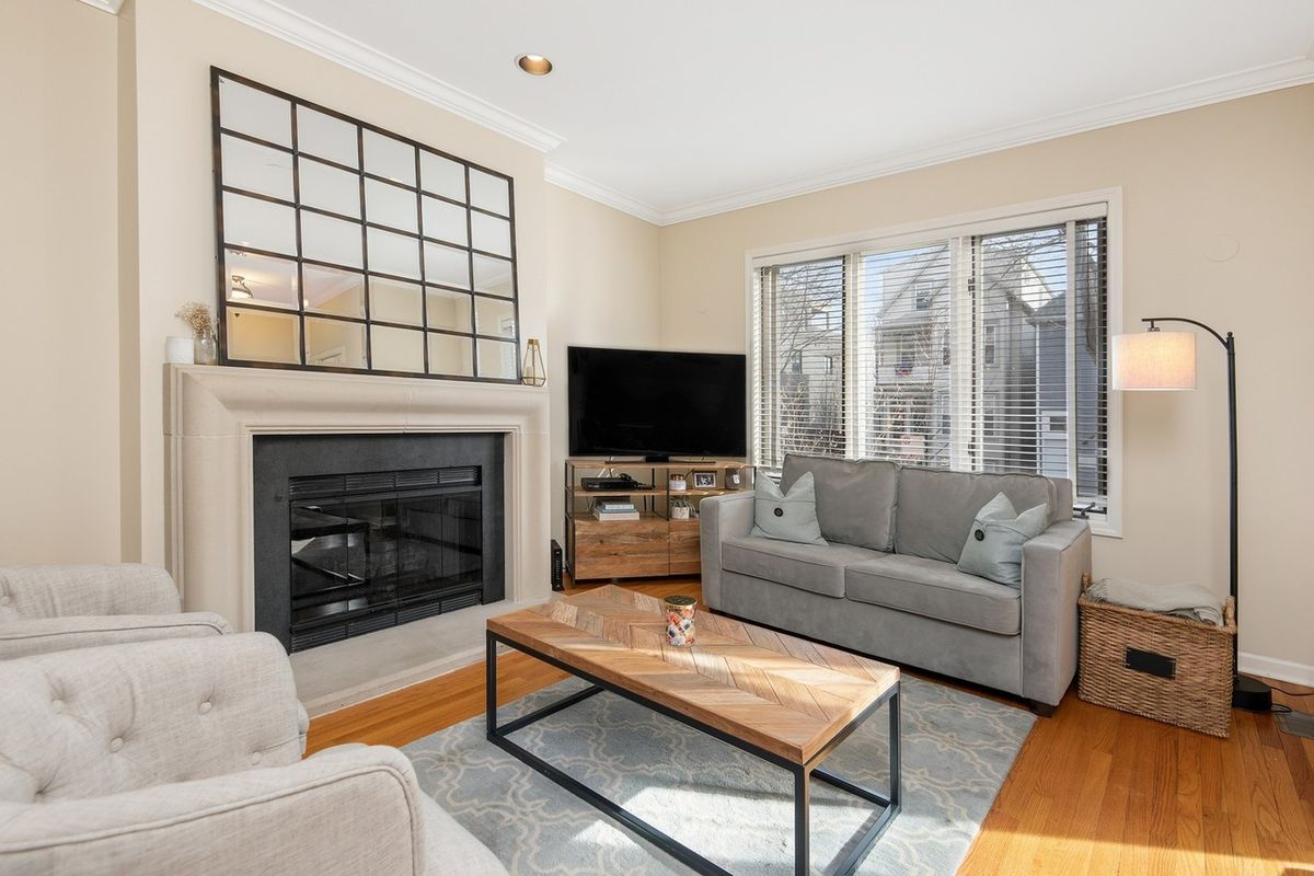 A living room with a couch and two chairs. There is a fireplace, a coffee table, and a large paned mirror.