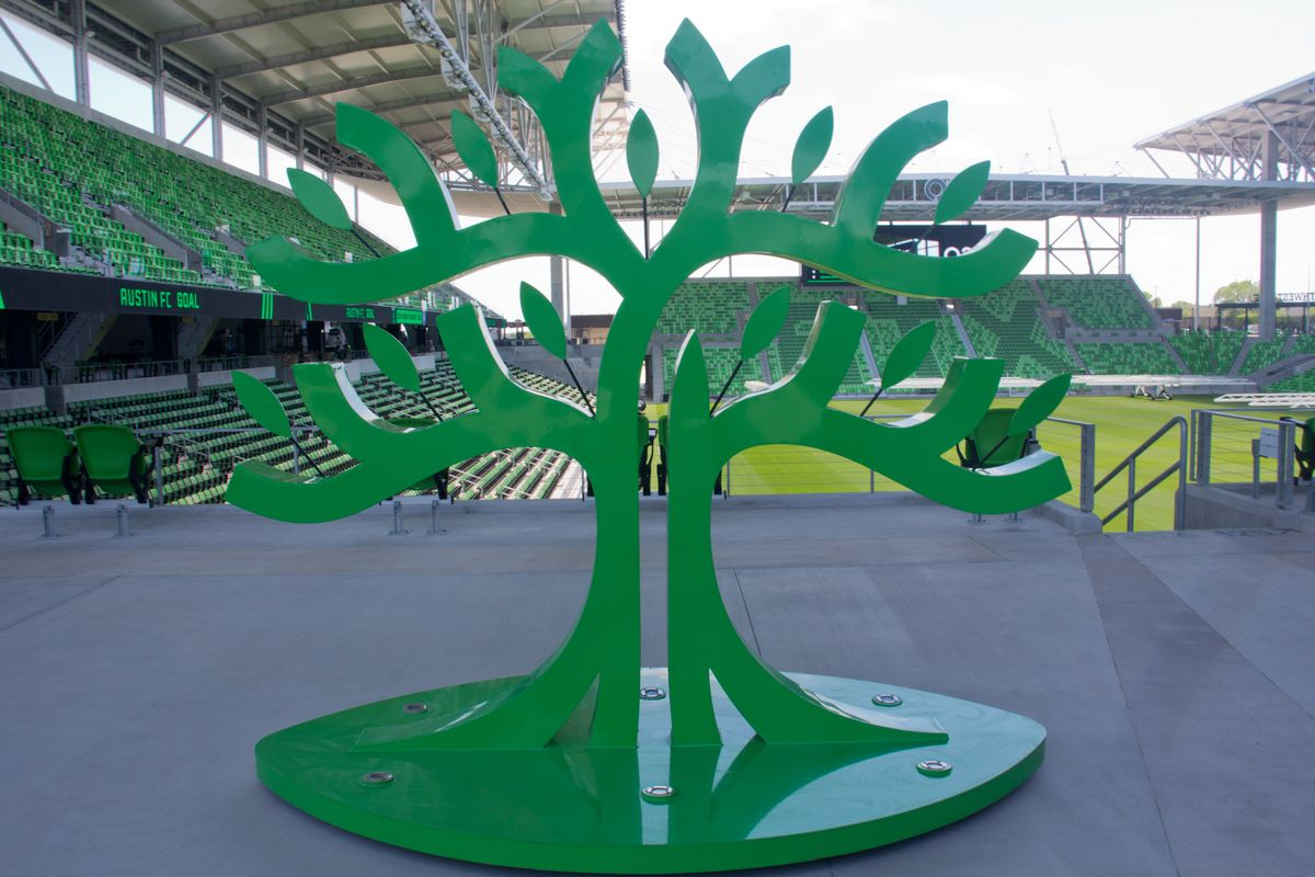 A green cut-out statue of a tree in a soccer stadium