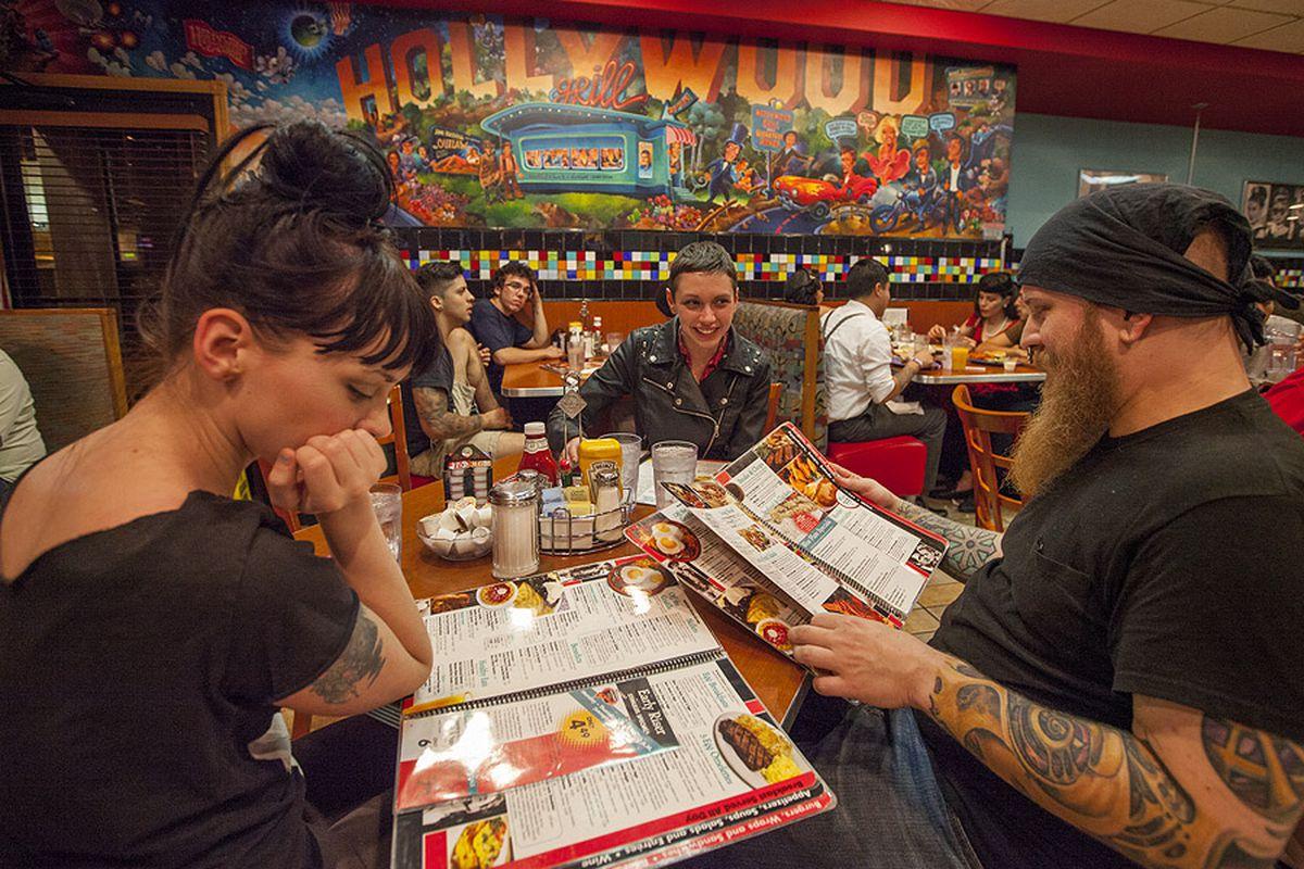 Three folks eating at diner.